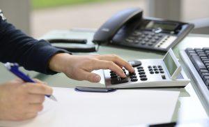Frau kalkuliert am Schreibtisch mit Taschenrechner